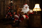 Santa Claus sitting at home near Christmas tree and  resting