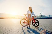 stock photo of bicycle gear  - Attractive young woman with fixed gear bike posing outdoors with soft sunset light on background p - JPG