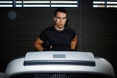 Fit man running in a gym on a treadmill looking to the screen