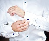 Man wears cuff-links on a shirt sleeve. A groom putting on cuff-links as he gets dressed formal wear