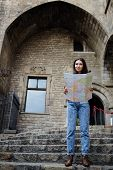 foto of gothic female  - Beautiful tourist woman on vacation with a map in antique gothic city young traveler girl searching right direction on city map pretty young female tourist studying a map standing in gothic quarter - JPG