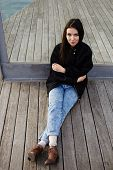 Attractive student girl seated on wooden pier having class break