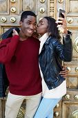 pic of san valentine  - Stylish couple having fun making self portrait picture on digital camera of mobile phone woman kissing boyfriend on the cheek photographing themselves with smartphone couple in love on san valentine - JPG