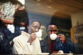 Постер, плакат: friends at breakfast having coffee and enjoying themselves two young friends holding cups of coffee