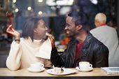Portrait of young couple in love at a coffee shop boyfriend wiping her mouth with a napkin