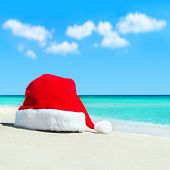 Red Santa Hat On White Tropical Beach Sand - Christmas Or New Year's Concept