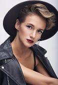 Portrait of sensual woman in hat leather jacket in studio