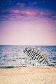 Striped Umbrella On Sandy Beach