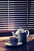 tea cup with teapot on old wooden table against the background o