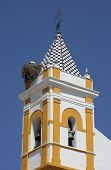 stock photo of blue-bell  - Typical bell tower on a little town of Seville province over blue sky - JPG