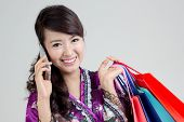 Asian shopping woman using smart phone and holding colorful shopping bags