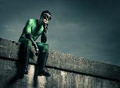 Pensive Superhero Against Dark Sky