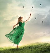 picture of chase  - Beautiful woman in a green dress chasing butterflies on a mountain - JPG