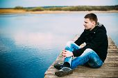 Young Handsome Man Sitting On Wooden Pier, Relaxing,  Thinking, Listening. Casual Style - Jeans, Jac