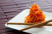 foto of fermentation  - small serving of fermented carrots served on a small white plate with chop sticks