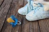 baby shoes and a pacifier on the old wooden background.