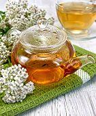 Tea with yarrow in glass teapot on board