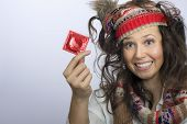 Girl With A Knitted Hat And A Red Condom Pack In The Hand