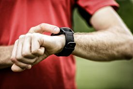 image of check  - Runner on mountain trail looking at smartwatch or sport watch checking gps navigation position map or heart rate pulse trace using heart monitor equipment - JPG