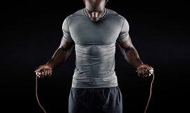 stock photo of roping  - Muscular man skipping rope - JPG
