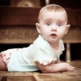 foto of shock awe  - Surprised Little Baby on the Floor in Home Interior - JPG