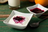 stock photo of fruit bowl  - Horizontal photo of Red berry fruit in white yogurt placed with bowl on green table and second bowl orange and glass of milk in background plus spoon on right. [[** Note: Shallow depth of field ** Note: Visible grain at 100%, best at smaller sizes - JPG