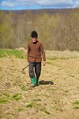 stock photo of hoe  - Senior man with a hoe in his hand walking to a field - JPG