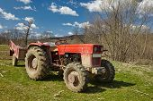 stock photo of tractor-trailer  - Old dirty tractor with trailer on a field - JPG