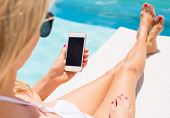 picture of sunbather  - Woman sunbathing in chair by the pool and using mobile phone - JPG
