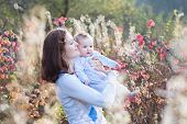 foto of mother baby nature  - Young Mother And Her Baby Standing In A Meadow On A Sunny Autumn Day - JPG