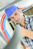 stock photo of hvac  - Electrician working through an open ceiling hatch - JPG