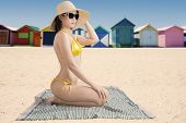 stock photo of swimsuit model  - Beautiful sexy model wearing swimsuit while sitting at beach on mat with the background of the beach cottage - JPG
