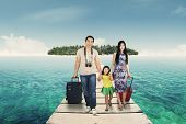 pic of carry-on luggage  - Portrait of happy family arriving at the resort and walking on the wooden bridge with their luggage - JPG