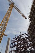 stock photo of tatas  - A view of a yellow tower crane and red steel and concrete structure on a building site - JPG