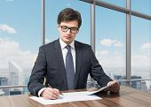 picture of diligent  - Handsome legal consultant is dealing with due diligence process in a modern skyscraper office with a panoramic New York view. ** Note: Shallow depth of field - JPG