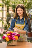 image of flower shop  - Young female florist making bouquet of flowers in shop - JPG