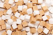 stock photo of sugar cube  - Cubes of sugar cane brown and white refined background - JPG