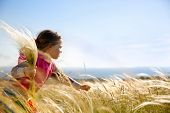 image of hay fever  - Cute little girl picking and gathering brown grasses on a meadow with the wind blowing through her long hair and sea in the background - JPG