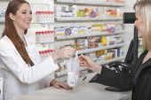 picture of sachets  - Friendly female pharmacist hands over a plastic sachet with medicine - JPG