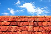 image of roof tile  - rusty tiles of old roof over blue sky - JPG