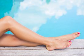 foto of painted toes  - Beautiful women legs by the swimming pool - JPG