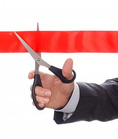image of pompous  - Hand of businessman in suit cutting red ribbon with pair of scissors isolated on white background - JPG