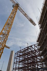 foto of tatas  - A view of a yellow tower crane and red steel and concrete structure on a building site - JPG