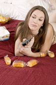 Attractive Young Woman In Bed Binge Eating
