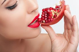 stock photo of pomegranate  - Close up of beautiful girl eating a pomegranate with pleasure - JPG