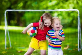 image of balls  - Two happy children playing European football outdoors in school yard - JPG