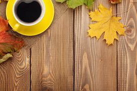 picture of coffee coffee plant  - Autumn leaves and coffee cup over wood background with copy space - JPG