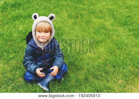 Cute kid resting outdoors sitting on a lawn playing on a rainy day wearing blue waterproof all-in-one suit