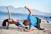 Fit couple doing intense workout on beach side planks strength training, healthy lifestyle poster