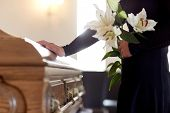 people and mourning concept - woman with white lily flowers and coffin at funeral in church poster
